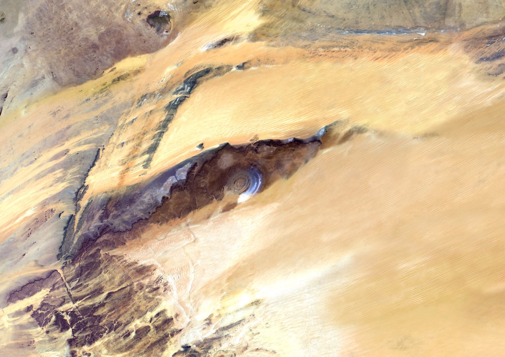 Stock Photo: 1899-34921 Richat Structure, Mauritania, True Colour Satellite Image. Richat Structure, Mauritania, true colour satellite image. The Richat structure is a geological formation in the Maur Adrar Desert in the African country of Mauritania. Although it resembles an impact crater, the Richat Structure formed when a volcanic dome hardened and gradually eroded, exposing the onion-like layers of rock. Image taken on 13 January 2003 using LANDSAT data.