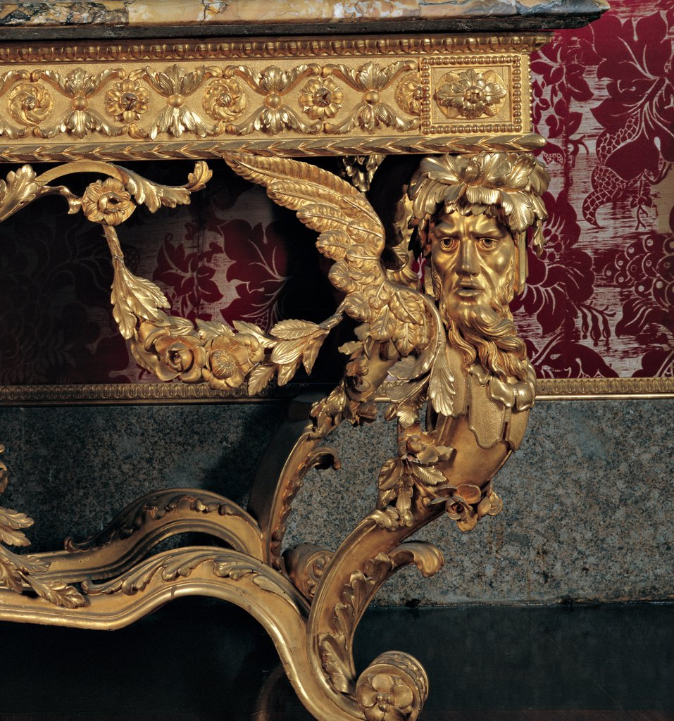 Wall table, by Lucca workmanship, 18th Century, Wood carved and gilded, giallo di siena marble. Italy: Tuscany: Florence: Palazzo Pitti: Palazzina della Meridiana. Detail. Wall table console furniture furnishing garlands imaginary creatures anthropomorphic figures winged figures branches leaves flowers gold wood gilt decoration : Stock Photo