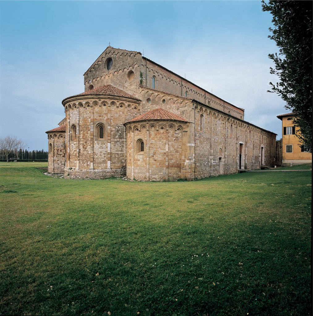 San Piero a Grado near Pisa, by Unknown artist, 10th Century, Livorno tufa, local limestone and salvaged materials. Italy: Tuscany: Pisa: San Piero a Grado. Whole artwork. Exterior church side apses stone pilaster-strips cornice hanging arches sloping roof projecting facade windows one-light windows oculus : Stock Photo