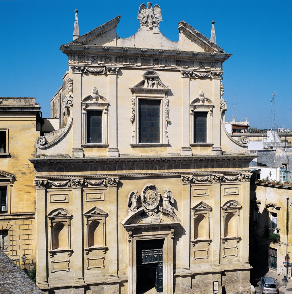 Stock Photo: 1899-46614 Church of the Gesu in Lecce, by De Rosis Giovanni, 1575 - 1577, 16th Century, . Italy: Puglia: Lecce: Lecce: Gesu Church. Whole artwork. Exterior Church of Gesu facade two-tiers architecture Ionic pilaster doorway crest/coat of arms Company of Jesus Jesuits monogram of Christ statues angels niches cornices string-course fastigium/pediment tympanum/gable broken pediment pelican Doric frieze