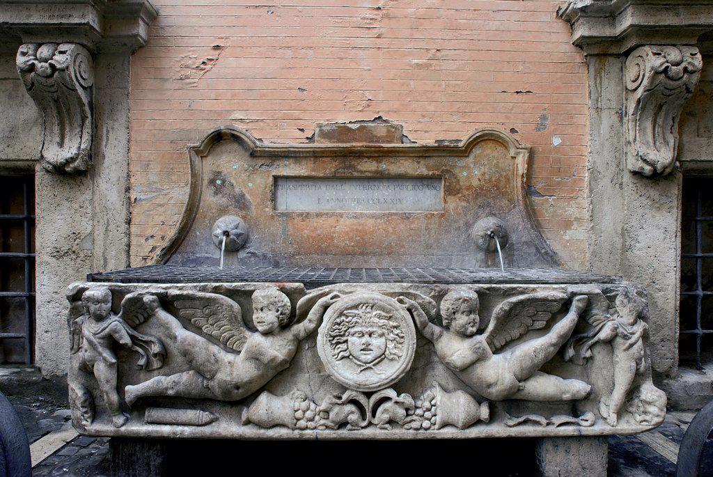 Stock Photo: 1899-46983 Fountain in Via Santo Stefano del Cacco, by Unknown artist, 17th Century, . Italy: Lazio: Rome: Via Santo Stefano del Cacco. View fountain winged putti Medusa basin sarcophagus inscription