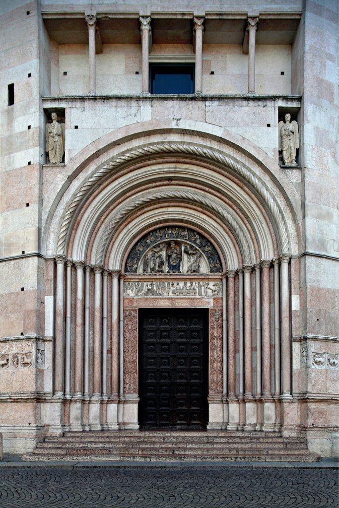 Parma Cathedral, Baptistery, by Antelami Benedetto, 1196, 12th Century, . Italy: Emilia Romagna: Parma: Baptistery. Exterior baptistery doorway slender columns angels tympanum bas-reliefs niches : Stock Photo