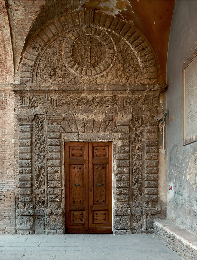 Oratory of the Cave, by Unknown artist, 16th Century, . Italy: Marche: Pesaro Urbino: Urbino: Grotta Oratory. Doorway rustication/ashlar-work symbol of the Company of Humility lunette travertine triglyphs decoration : Stock Photo