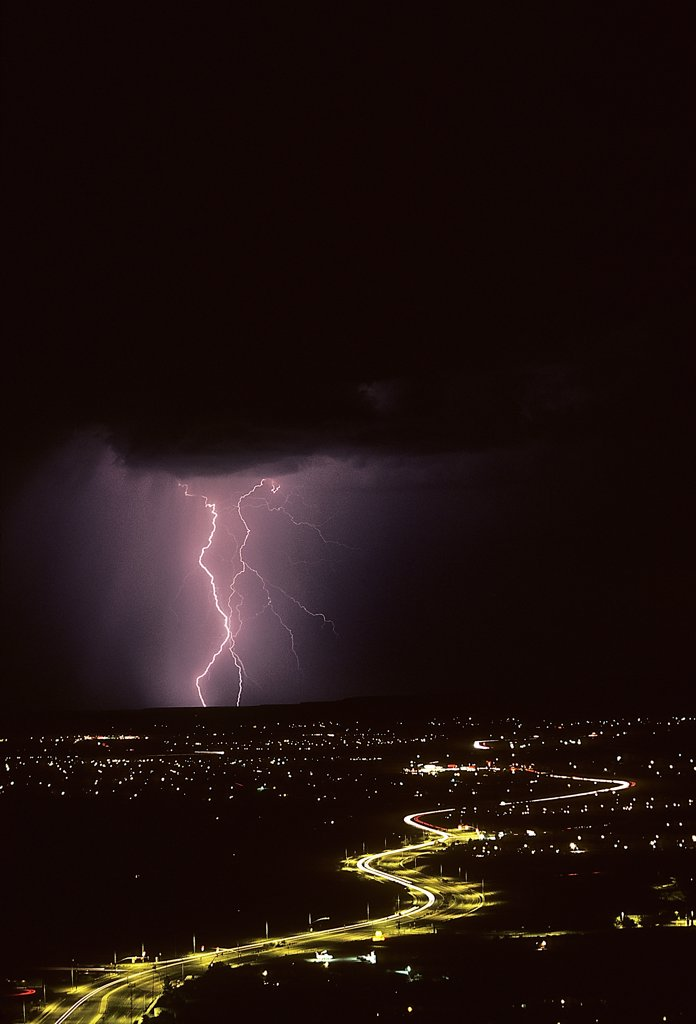 Stock Photo: 1899-49806 Cloud-to-ground lightning with city lights.   Tucson, Arizona, USA.
