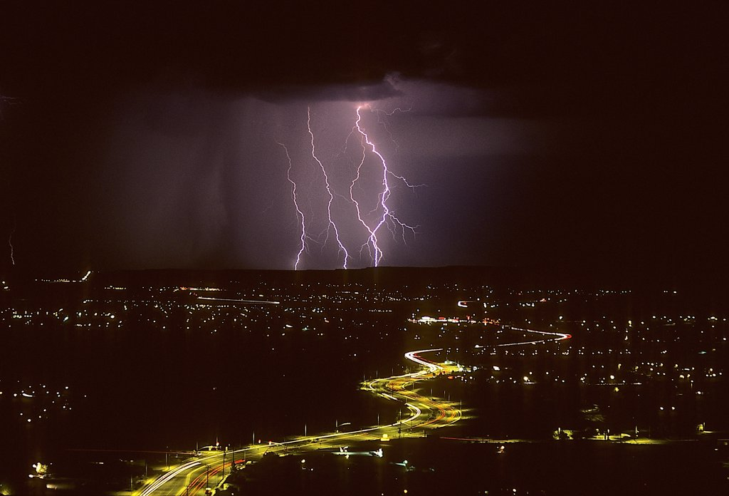 Stock Photo: 1899-49808 Cloud-to-ground lightning with city lights.   Tucson, Arizona, USA.