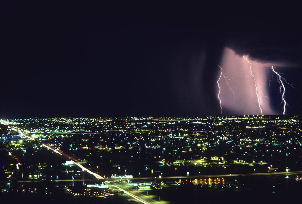 Stock Photo: 1899-49822 Storm front with lightning on the horizon over city.   Tucson, Arizona, USA.