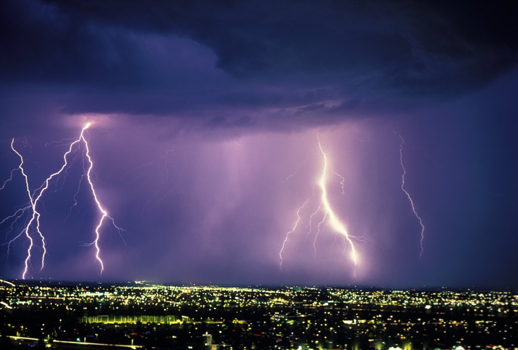 Stock Photo: 1899-49838 A 30-second exposure of an active storm cell with multiple cloud-to-ground discharges over city at night.   Tucson, Arizona, USA.