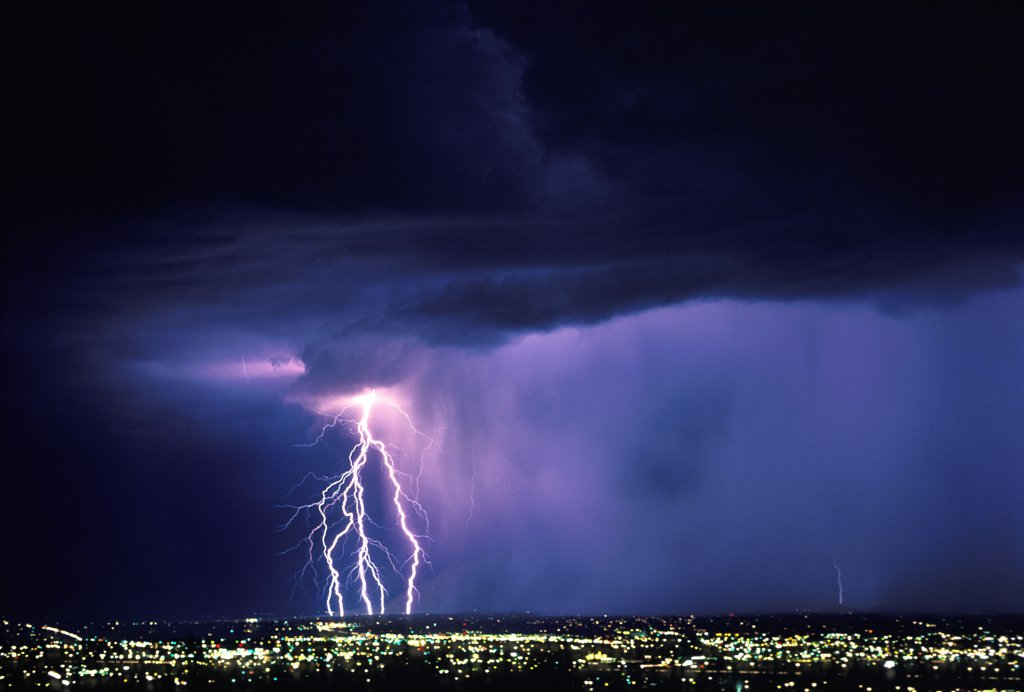 Stock Photo: 1899-49840 Five cloud-to-ground lightning strikes on leading edge of rain curtain sweeping over city at night.   Tucson, Arizona, USA.