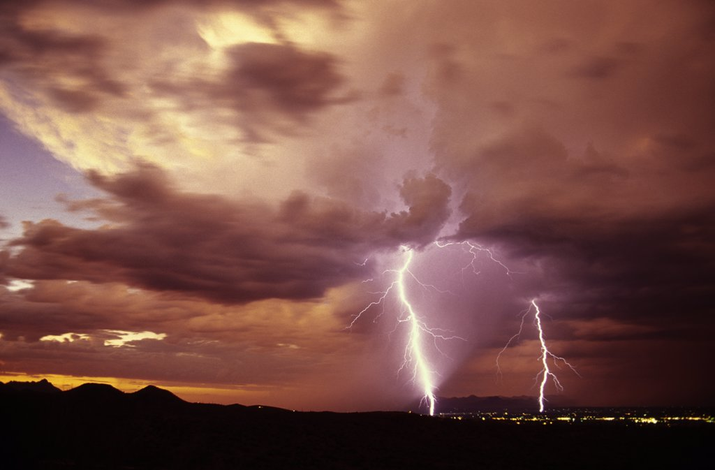 Stock Photo: 1899-49855 Sunset storm as seen from the Tucson Mountains looking northwest, with two cloud-to-ground lightning strikes, one within a rain shaft.   Tucson, Arizona, USA.