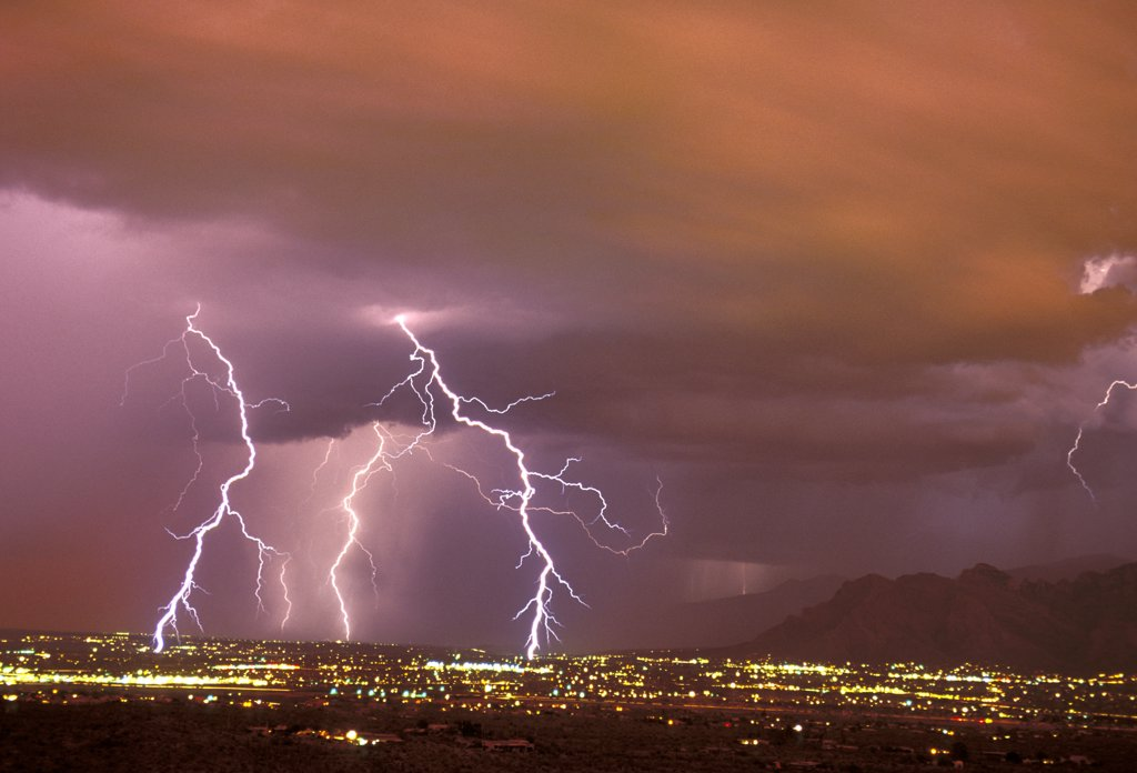 Stock Photo: 1899-49856 Sunset storm as seen from the Tucson Mountains looking northwest, with multiple cloud-to-ground lightning strikes in the city due west of the Santa Catalina Mountains.   Tucson, Arizona, USA.