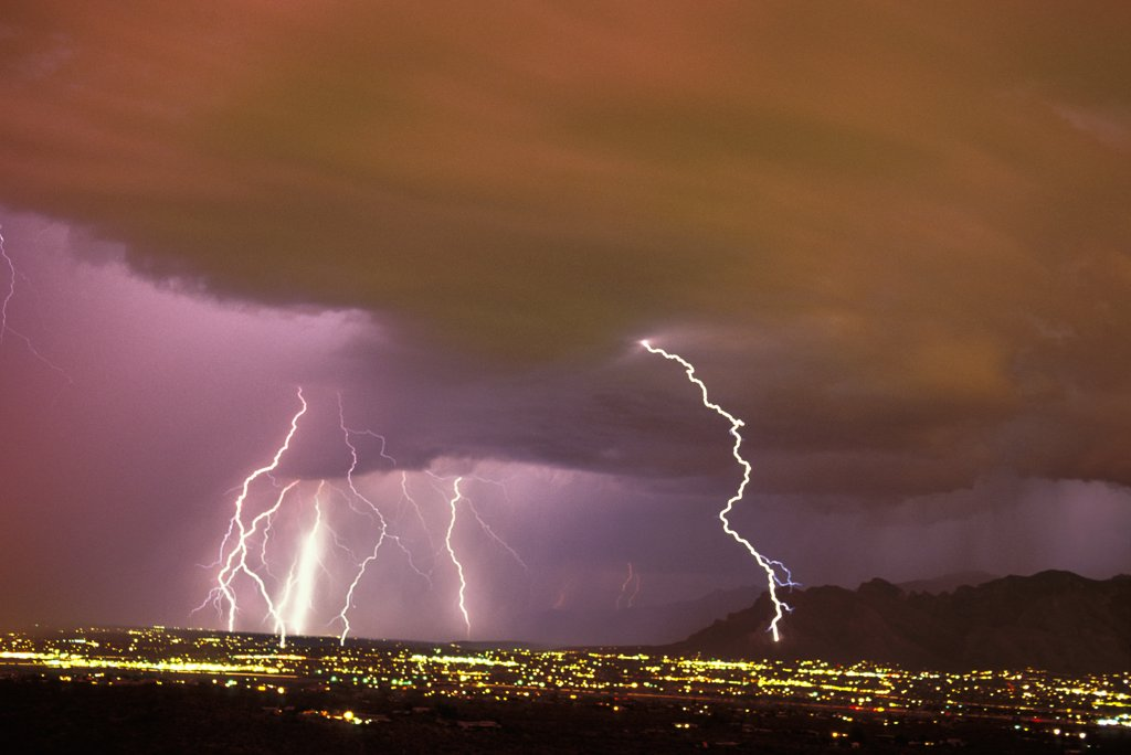 Sunset storm as seen from the Tucson Mountains looking northwest, with multiple cloud-to-ground lightning strikes in the city due west of the Santa Catalina Mountains.   Tucson, Arizona, USA. : Stock Photo