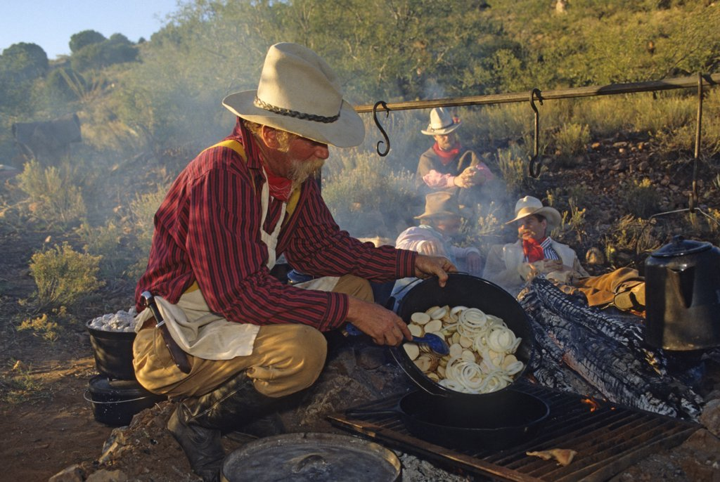 Stock Photo: 1899-49879 Chuckwagon cook Mike Ryan prepares breakfast (frying potatoes and onions) at cowboy camp.  Cattle drive organized by Dan Bates, Cobra Ranch, Agro Land and Cattle Company. Galiuro Mountains, Arizona, USA. October 1993    In background: rear, Thomas Hirt (a Tucson hatmaker); right, Dan Bates; left front, John Cleator, Jr.