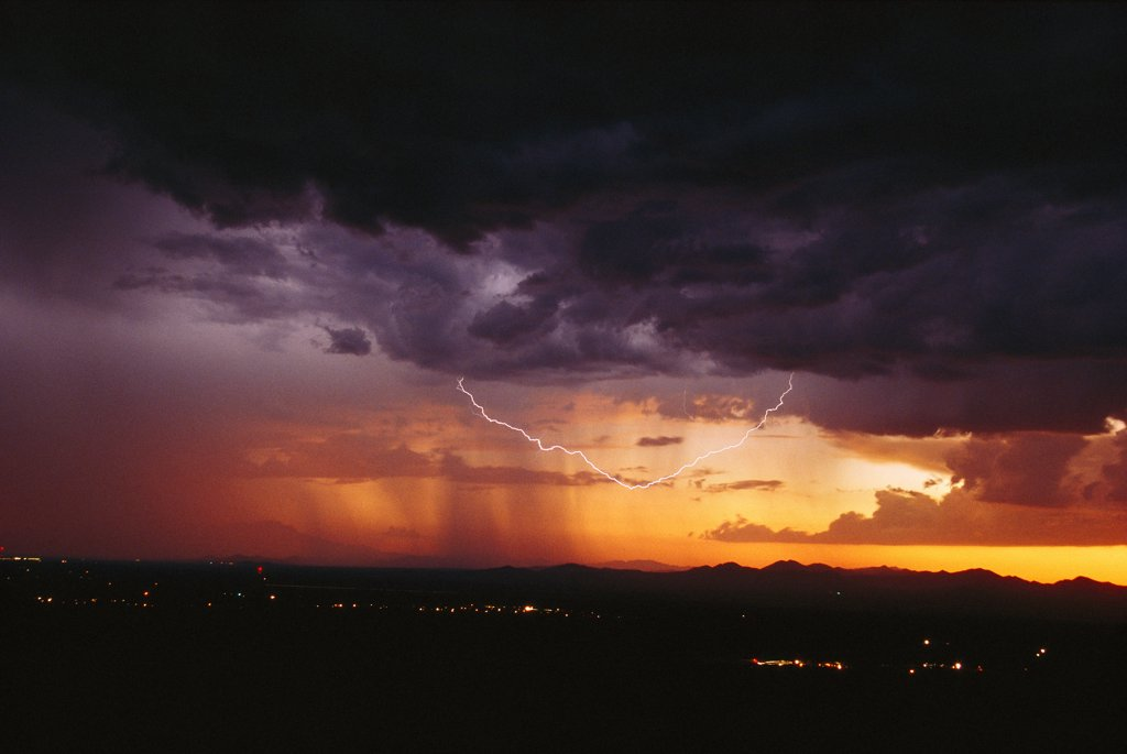 Arc of cloud-to-cloud lightning below the cloud base at sunset. This is a rare shot of scientific interest, as it appears to represent a single discharge channel.    Avra Valley, Arizona, USA. : Stock Photo