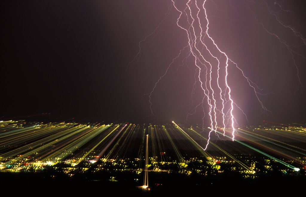 Stock Photo: 1899-50017 View of separated lightning strokes in a cloud-to-ground lightning strike over city at night.  This picture of scientific interest was made possible by zooming a photographic lens during the full interval of the lightning flash, thereby separating and recording on film each electrical stroke contained within the strike.  And the effect of zooming records the city lights as streaks across the film. Tucson, Arizona, USA.