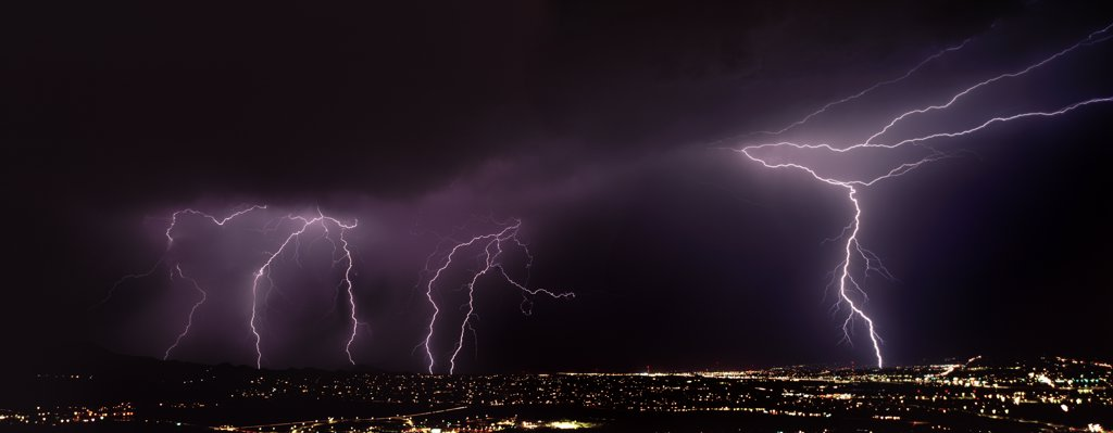 Stock Photo: 1899-50054 On right, two types of lightning from one forked channel, cloud-to-air and cloud-to-ground discharges.  Summer monsoon season. Tucson, Arizona, USA.  Panoramic 6x17 film