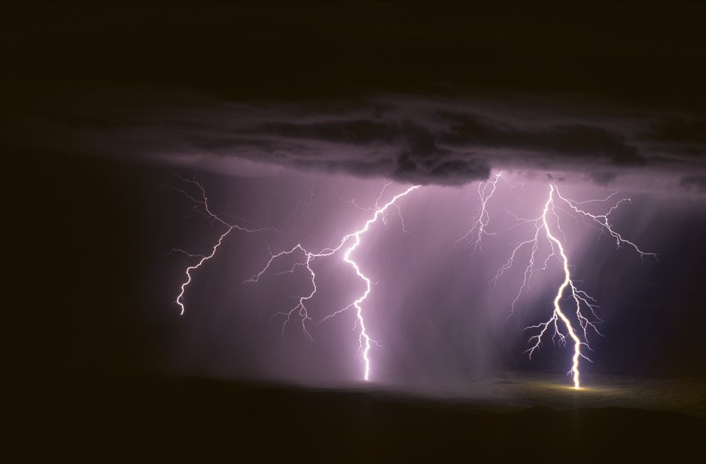 Stock Photo: 1899-50280 Two powerful cloud-to-ground lightning discharges at the leading edge of a rain curtain.   Plains of San Agustin, New Mexico, USA.