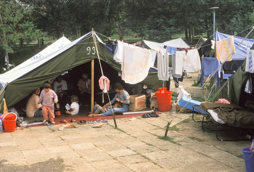 Stock Photo: 1899-50477 Albania, Tirana, Swimming Pool Camp For Kosovo Refugees. Women And Children In Tent With Laundry Hanging Outside. 1999