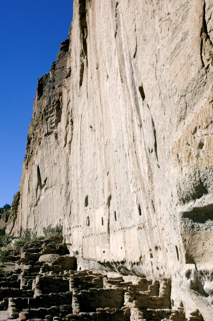 New Mexico, Bandelier National Monument. Frijoles Canyon. Main Loop Trail. Showing The Archeological Features Left By The Ancestral Pueblo People (Anasazi). Long House Ruins Along The Eroded Canyon Cliff Face. : Stock Photo
