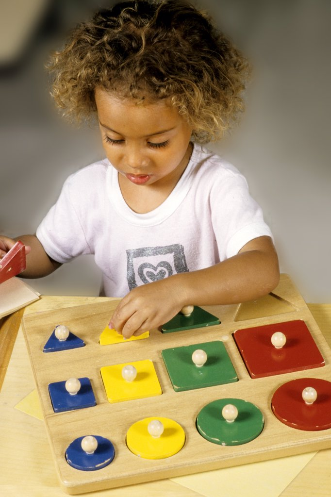 Stock Photo: 1899-52190 Girl Working With Blocks To Learn Shapes