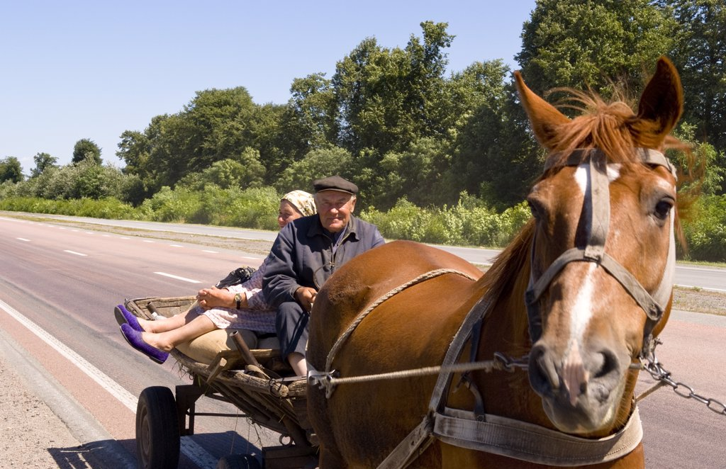 Stock Photo: 1899-52597 Farming Couple Riding On Horse-Drawn Cart On Road From Kiev To Lviv In The Ukraine
