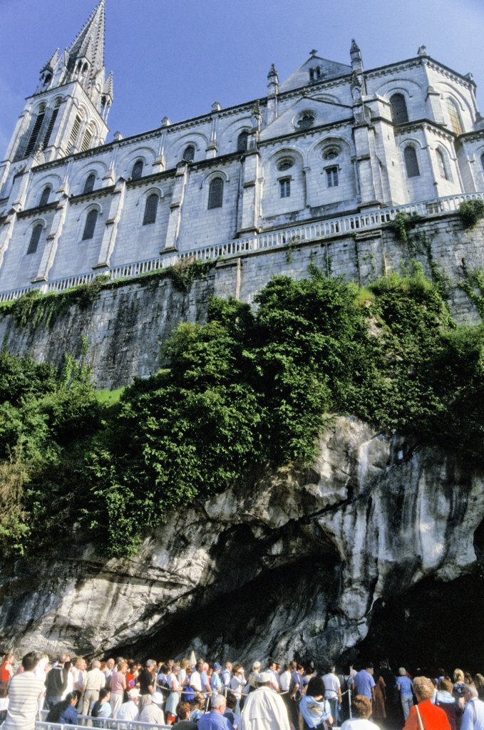Stock Photo: 1899-53611 France. Lourdes.Church Above And Pilgrims Waiting To Enter The Grotto Of Miraculous Appearances Of Our Lady (Grotte Massabielle).