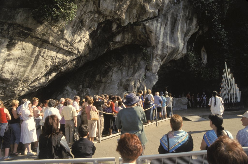 France. Lourdes.Pilgrims Waiting To Enter The Grotto Of Miraculous Appearances Of Our Lady (Grotte Massabielle). : Stock Photo