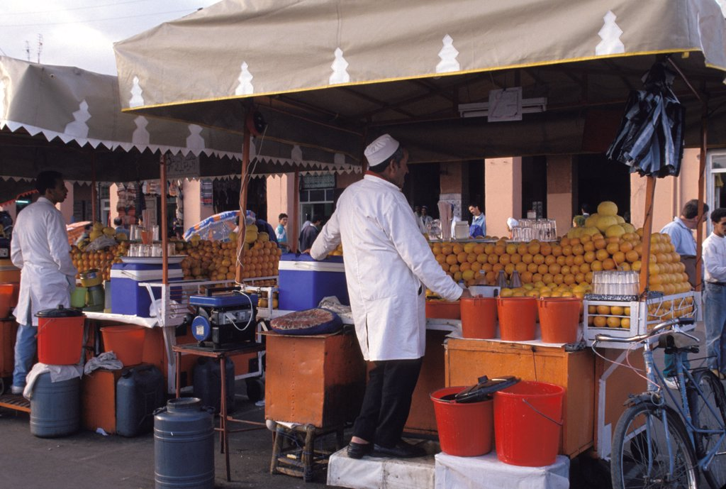Stock Photo: 1899-58085 Morocco, Marrakesh. Men At Outdoor Stands Selling Fresh Orange Juice.