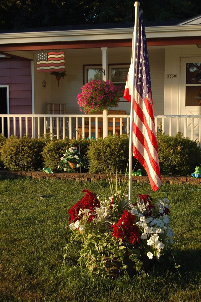 American Flag In Front Of Home. : Stock Photo
