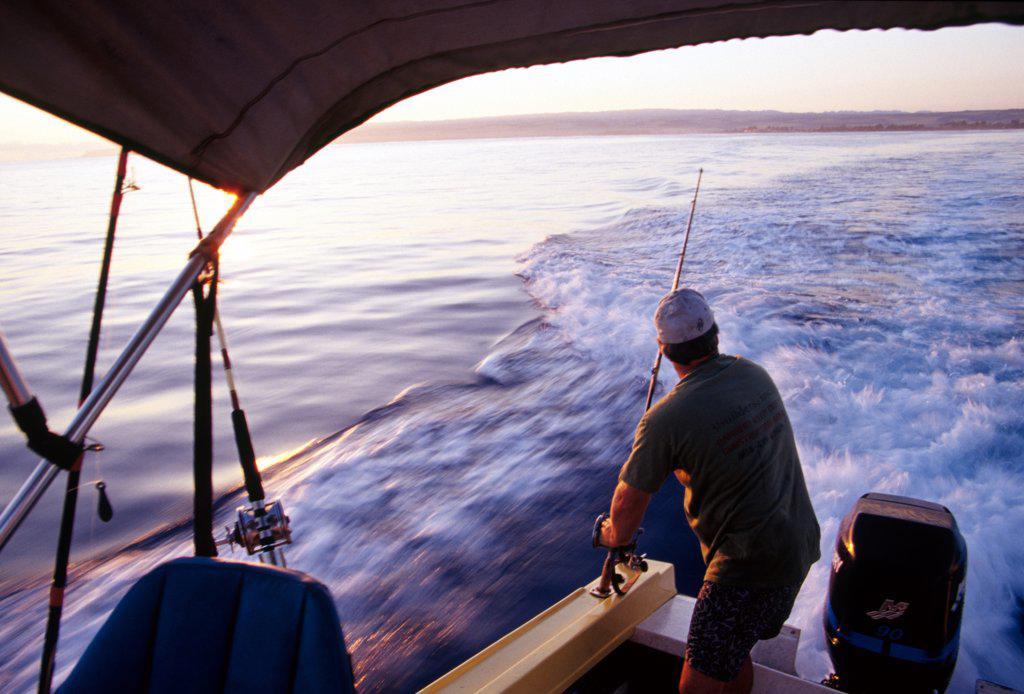 Man Rigging Deep Sea Fishing Poles On Fishing Boat Off The North Shore Of Oahu, Hawaii. : Stock Photo