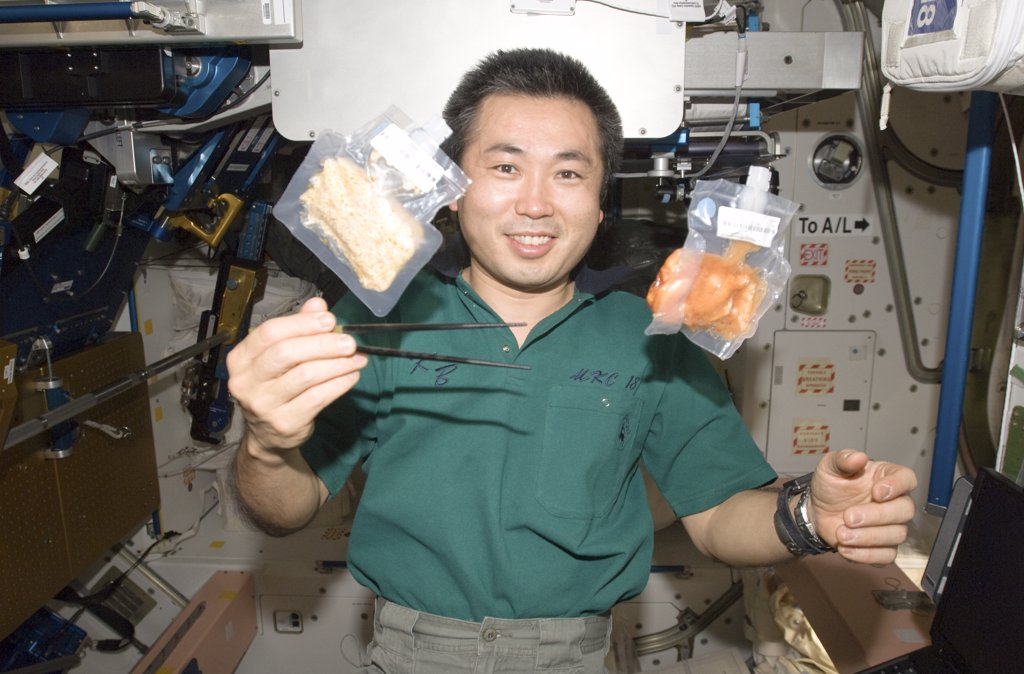 Stock Photo: 1899-60894 3 June 2009. Japan Aerospace Exploration Agency (Jaxa) Astronaut Koichi Wakata, Expedition 20 Flight Engineer, Holds Chopsticks Near Two Food Containers Floating Freely In Unity Node Of The International Space Station.