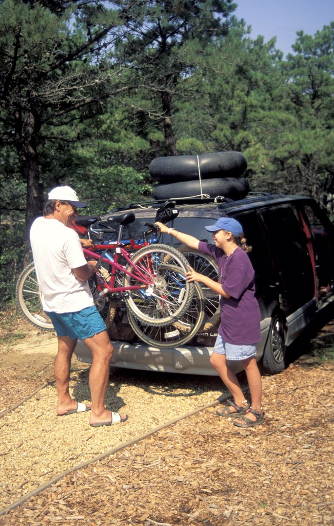 Father And Daughter Loading Minivan With Bikes And Inner Tubes : Stock Photo