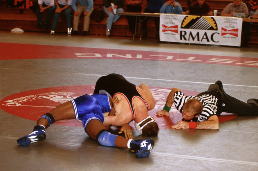 Colorado, Gunnison. Referee Looks At Two Students Wrestling. Western State College. : Stock Photo