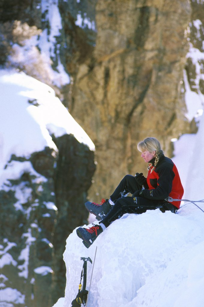 Stock Photo: 1899-62955 Colorado, Ouray. Ice Climbing, Woman Secured On A Ledge, Waits For Her Climbing Partner, Climbing Behind Her