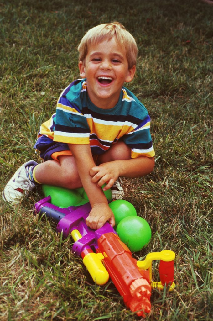 Five Year Old Blonde Little Boy With A Water Gun Smiling In A Backyard : Stock Photo