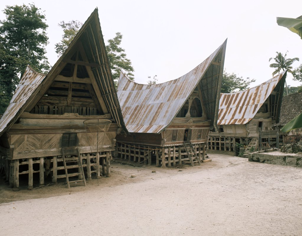 The three-level structure of Toba Batak houses corresponds to ideas of the cosmos, The lower space between the stilts where animals are kept is the underworld, the living area above is the Earth, the tall boat-shaped roof the abode of Gods and ancestors. Indonesia. Toba Batak. 1968. Lake Toba, North Sumatra. : Stock Photo