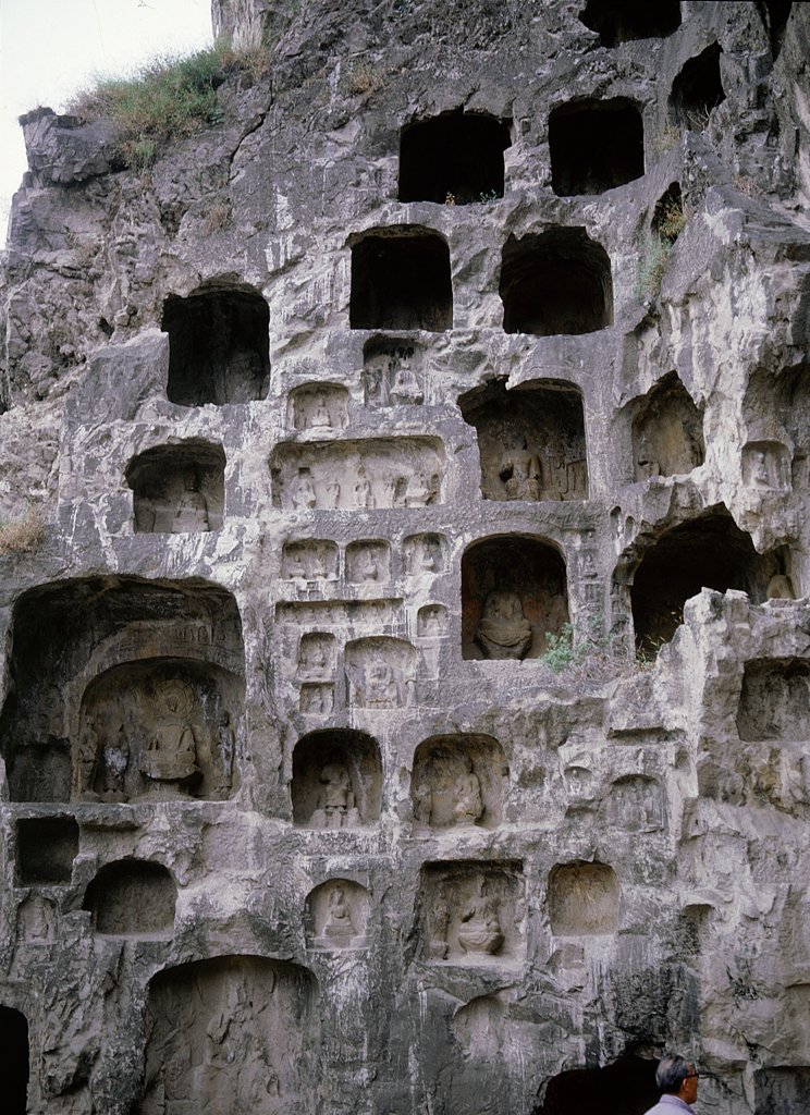 The Longmen cave-temple complex which extends for about 1000m along the Yi River, There are 1352 grottoes, over 750 niches and about 40 pagodas of various sizes. They contain more than 100,000 Buddhist images. Work on the caves began in about AD 494 and continued into the Tang period. China. Buddhist. near Luoyang, Henan province. : Stock Photo