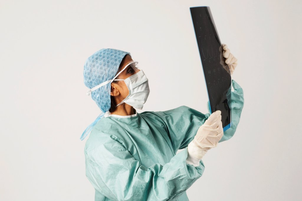 Stock Photo: 1899-64850 Surgeon examining set of x-rays