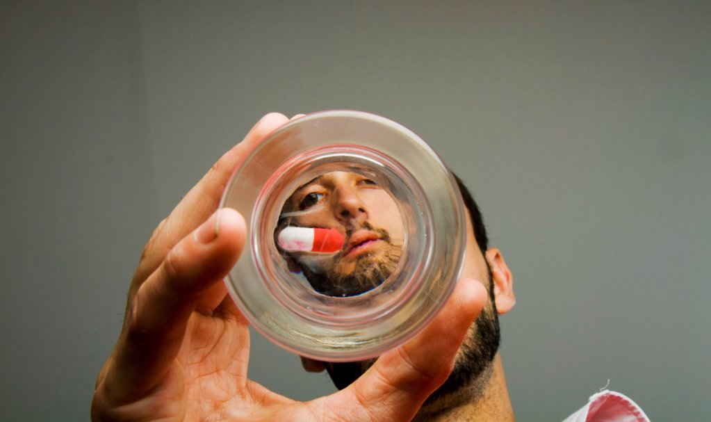 Man looking at pill at bottom of glass : Stock Photo