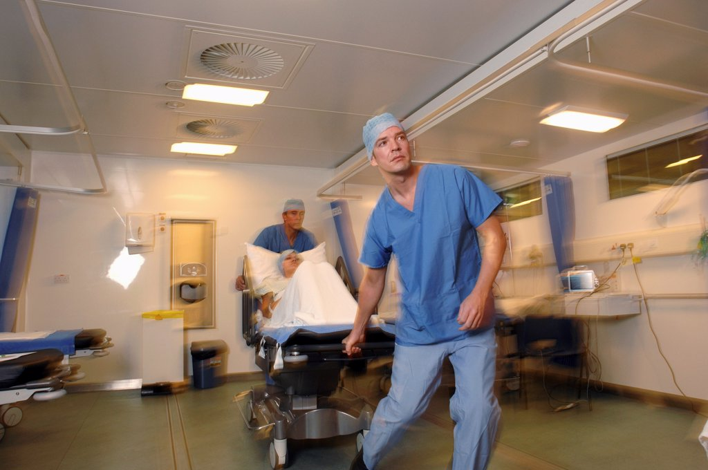 Stock Photo: 1899-66037 Two hospital porters wheeling patient on trolley bed