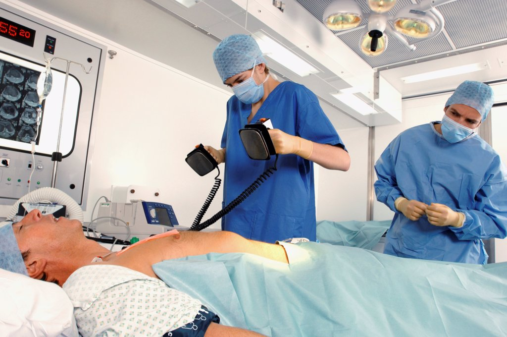 Stock Photo: 1899-66044 Doctors using defibrillator to resuscitate male heart