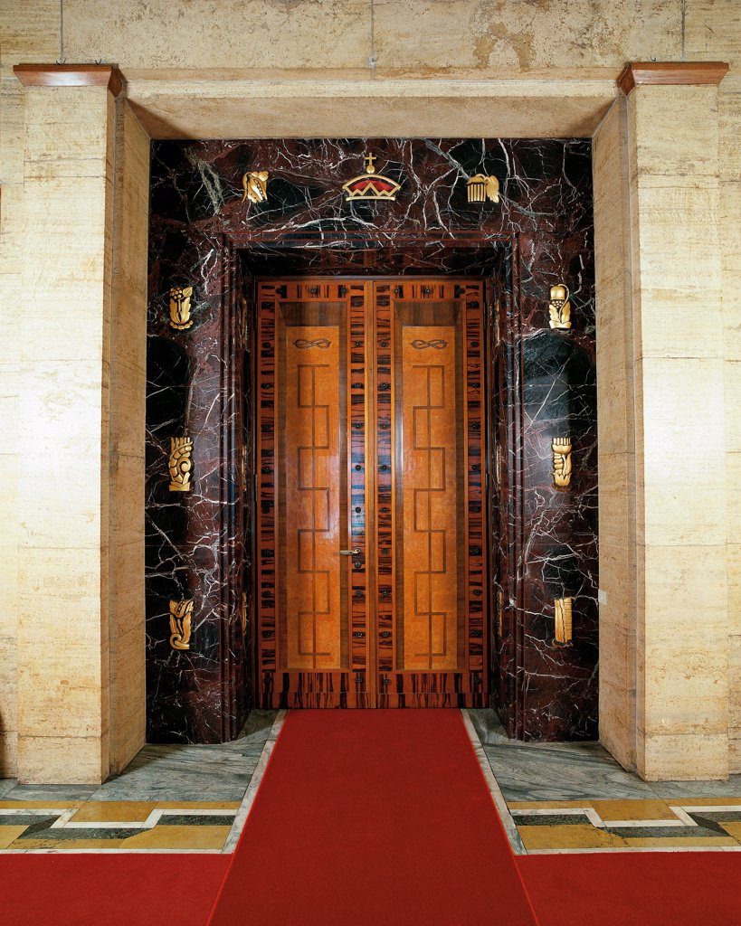 Italy, Trentino Alto Adige, Bolzano, Prefecture Palace. Detail. A door with a travertine splay with decorations in gilded bronze. The leafs are in carved wood. : Stock Photo