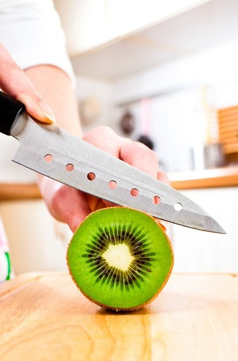 Stock Photo: 1899-88566 Close up of Person Slicing Kiwi
