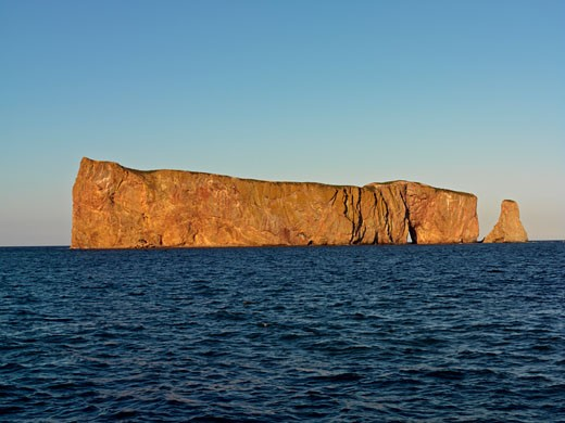 Canada Quebec Gaspesie Perce Perce Rock illuminated at sunset at high tide and the Gulf of Saint Lawrence : Stock Photo