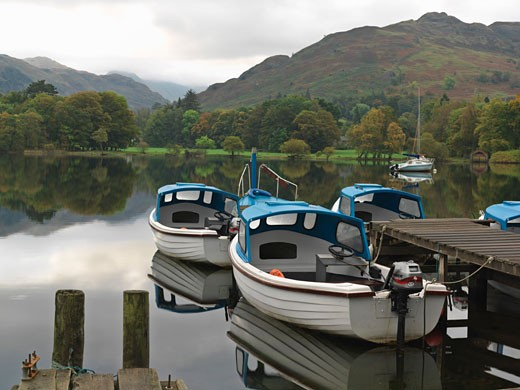 United Kingdom Cumbria Lake District National Park Ullswater Glenridding boats moored at dock for rent at Ullswater : Stock Photo