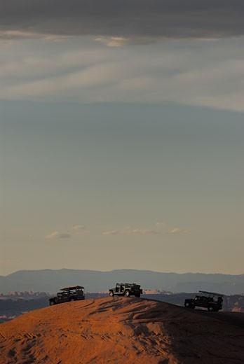Stock Photo: 1906-1925 Hummer jeeps on the slick rock trail near Moab Utah at sunset USA