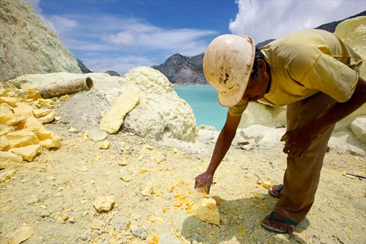 Stock Photo: 1907-1385 Sightseeing on the lake of the crater of the Kawa Ijan vulcano where a sulphur mine constantly smokes a sulphur worker is modeling some souvenirs in order to earn a few money with visitors Baluran national park Java Indonesia