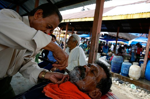 Hairdresser at the market of Parapat close to lake Toba Sumatra Indonesia : Stock Photo