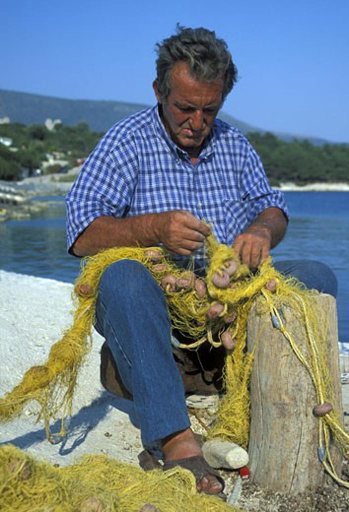 Stock Photo: 1909-2391 Greek Islands fisherman mending nets Cephalonia Ionian sea Greece Europe EU Portrait of Greek fisherman untangling his fishing nets in Fiskardo harbour Kefalonia Greece