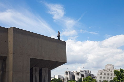 Stock Photo: 1909-2721 Anthony Gormley Sculpture Figure on Southbank building  looking toward the Shell Centre south bank Event Horizon Exhibition London England UK United Kingdom GB Great Britain British Isles Europe EU