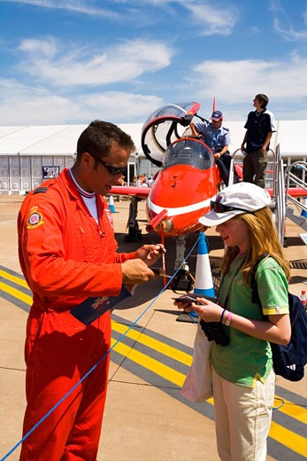 Red Arrows RAF aerobatic display team pilot signs autograph for lucky young girl at Fairford International Air Show 2006 Gloucestershire England Great Britain GB United Kingdom UK British Isles : Stock Photo
